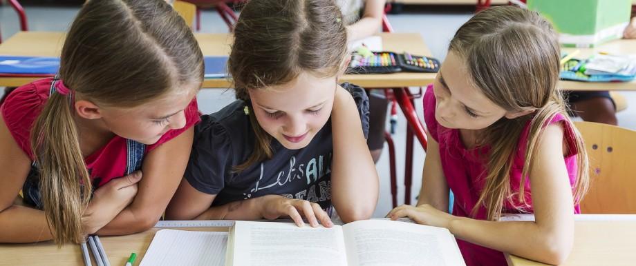 Three schoolgirls reading a book model released Symbolfoto property released PUBLICATIONxINxGERxSUIx