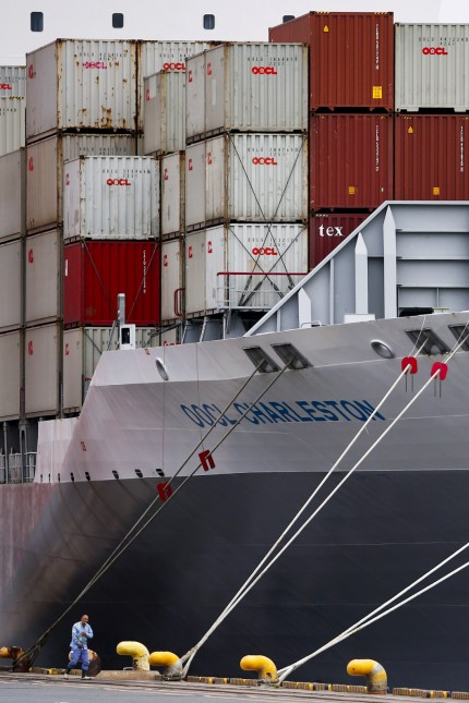 Man walks in front of container ship at port in Tokyo