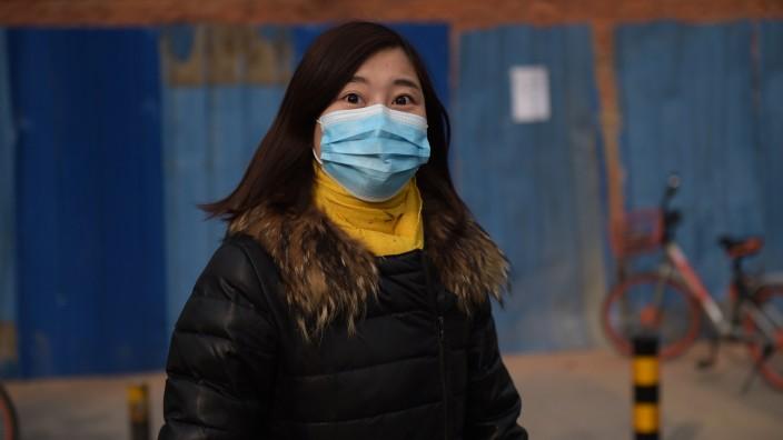China: Schutzmaske und Daunenjacke: Besonders im Winter wird die Luft in Chinas Städten schlecht.