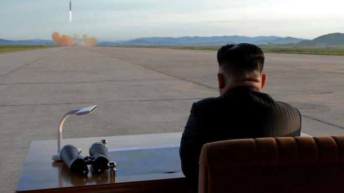 FILE PHOTO: North Korean leader Kim Jong Un watches the launch of a Hwasong-12 missile in this undated photo released by North Korea's KCNA