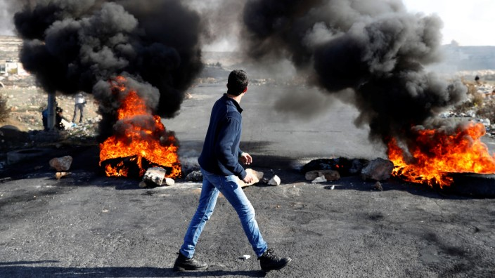 A Palestinian protester walks in front of a burned barricade during a protest against U.S. President Donald Trump's decision to recognize Jerusalem as the capital of Israel, near the Jewish settlement of Beit El, near the West Bank city of Ramallah