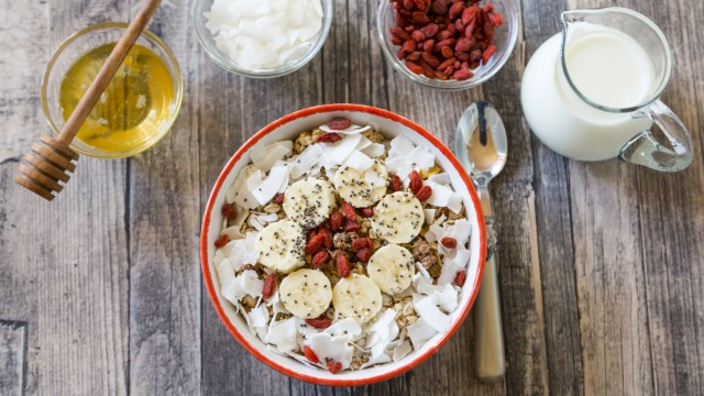Bowl of muesli with banana slices chia seeds coconut chips and goji berries PUBLICATIONxINxGERxSUI