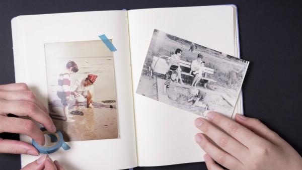 Two people sticking old fotographs in album model released Symbolfoto PUBLICATIONxINxGERxSUIxAUTxHUN
