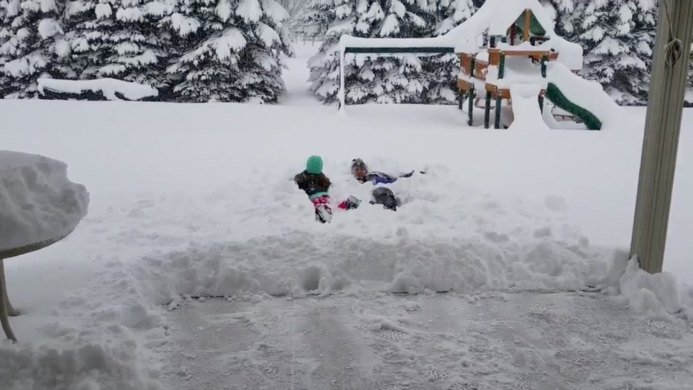People are seen lying in the snow after the record snowfall in Erie
