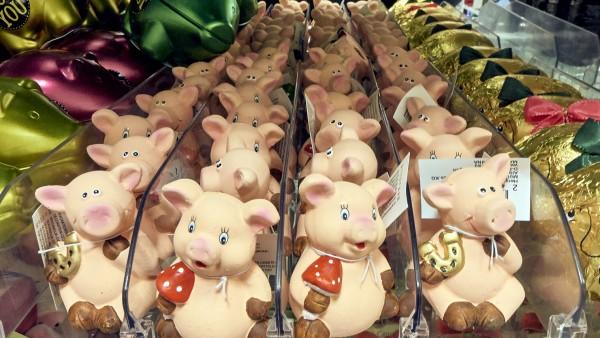 Man sieht viele Silvester-Glücksschweinchen mit Glückspilzen und Hufeisen.