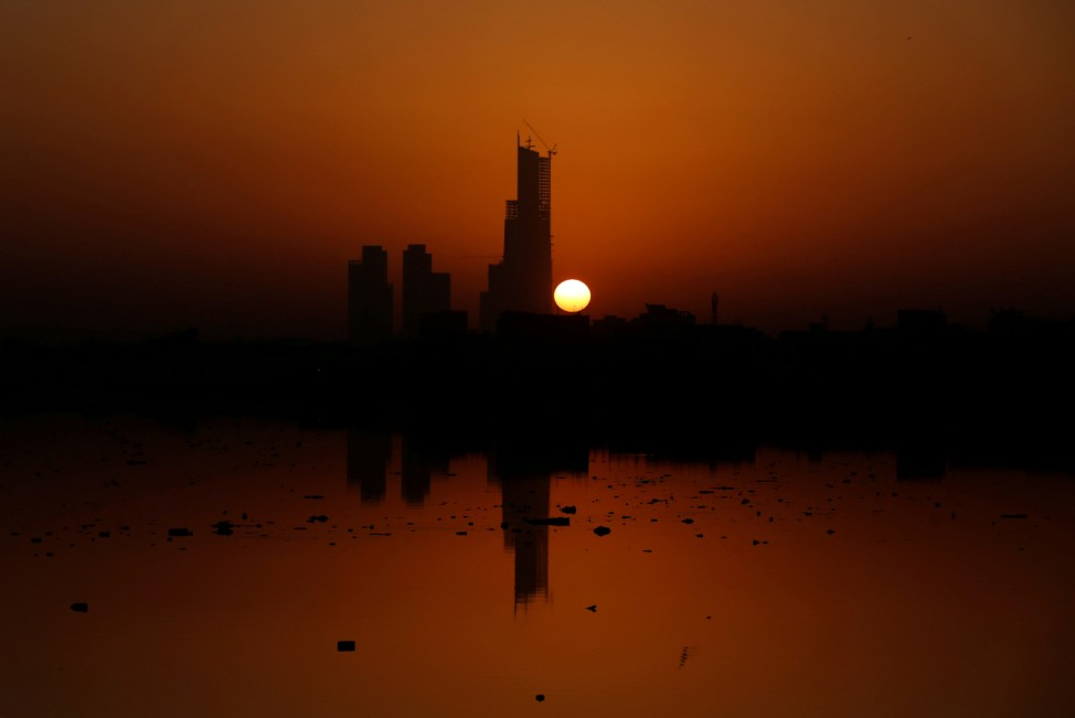 The first sun of the New Year rises behind the 62 storey Bharia Icon Tower, which is still under construction, in Karachi