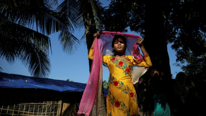 Taslima, a 13-year-old Rohingya refugee adjusts her scarf as she stands next to her temporary settlement at the Shamlapur refugee camp near Cox's Bazar