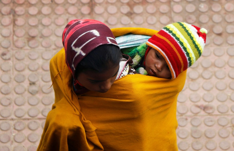 A woman wraps a child in a shawl while waiting for a train at a railway station on a foggy winter morning on the outskirts of Agartala