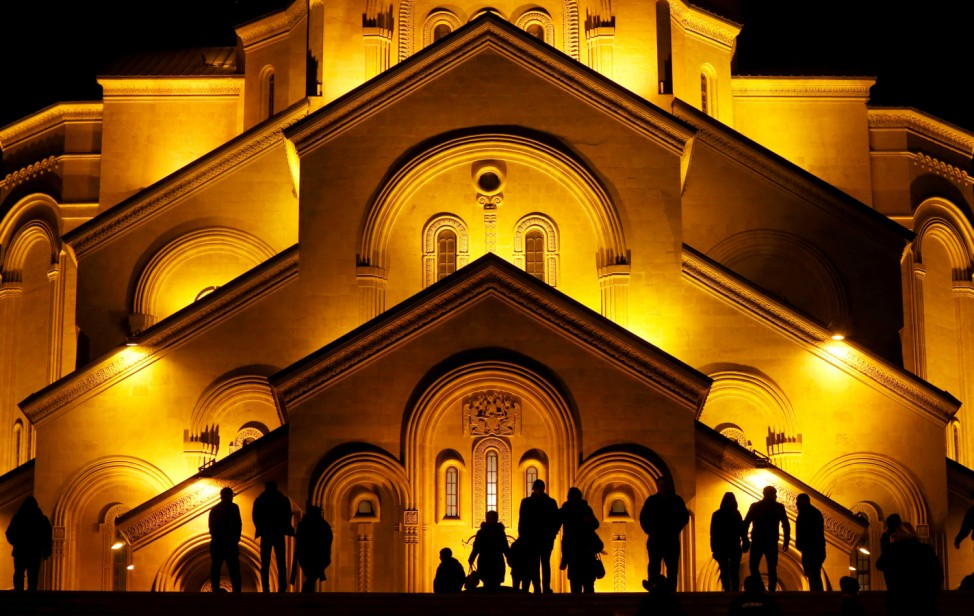 People walk in front of the Holy Trinity cathedral a midnight Christmas service in Tbilisi