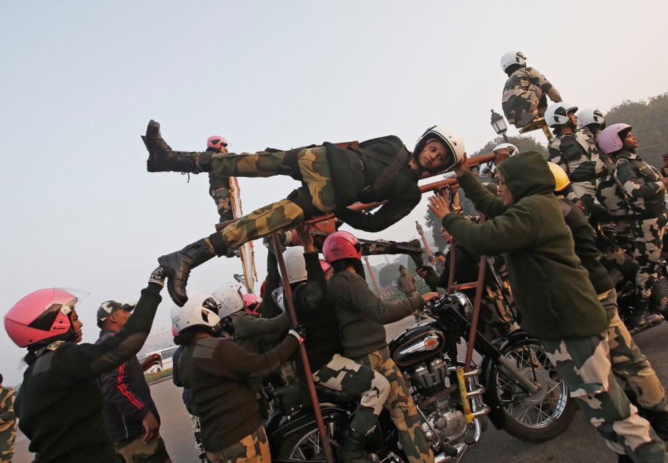 India's BSF 'Daredevils' women motorcycle riders help their colleague to balance on a bike during a rehearsal for the Republic Day parade on a cold winter morning in New Delhi