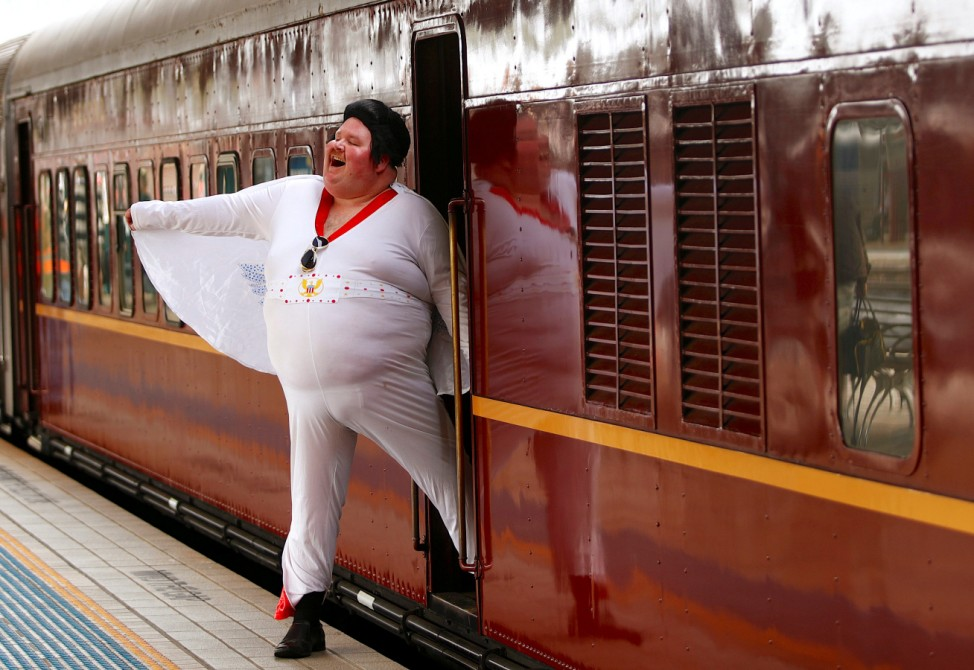 Elvis Presley impersonator Wright poses next to the Elvis Express train at Sydney's Central station before it departs for the 26th annual Elvis Festival