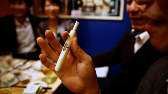 Ein Mann raucht mit Iqos in einem Restaurant