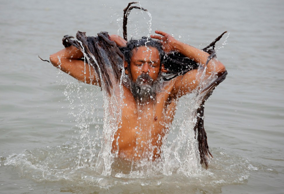 A Sadhu or a Hindu holy man takes a dip in the waters of the river Ganges on the occasion of 'Makar Sankranti' festival in Kolkata