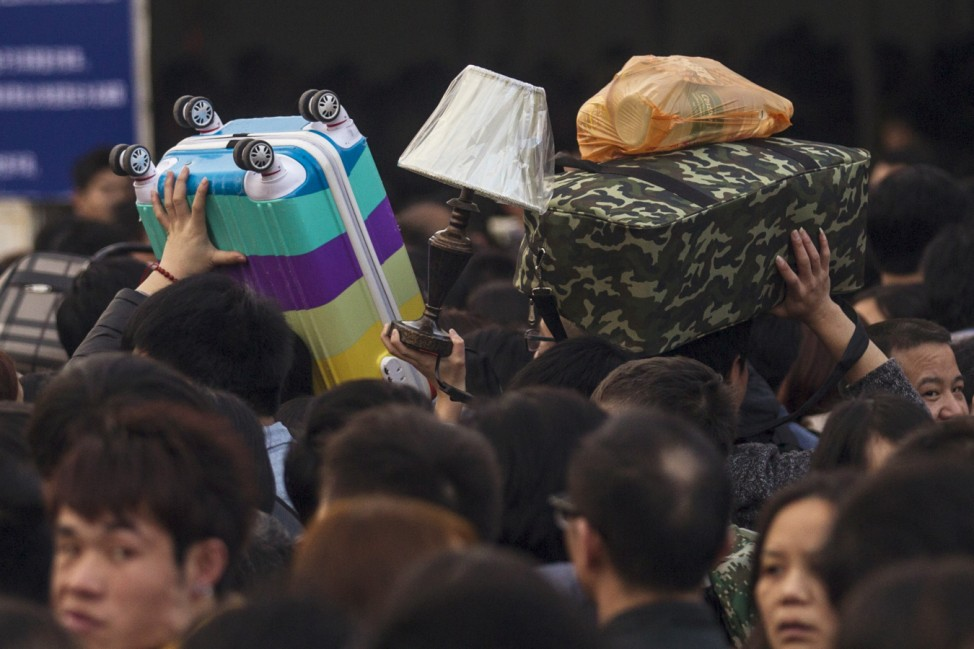 People carry their belongings toward trains at the main railway station in Guangzhou, Guangdong province, China