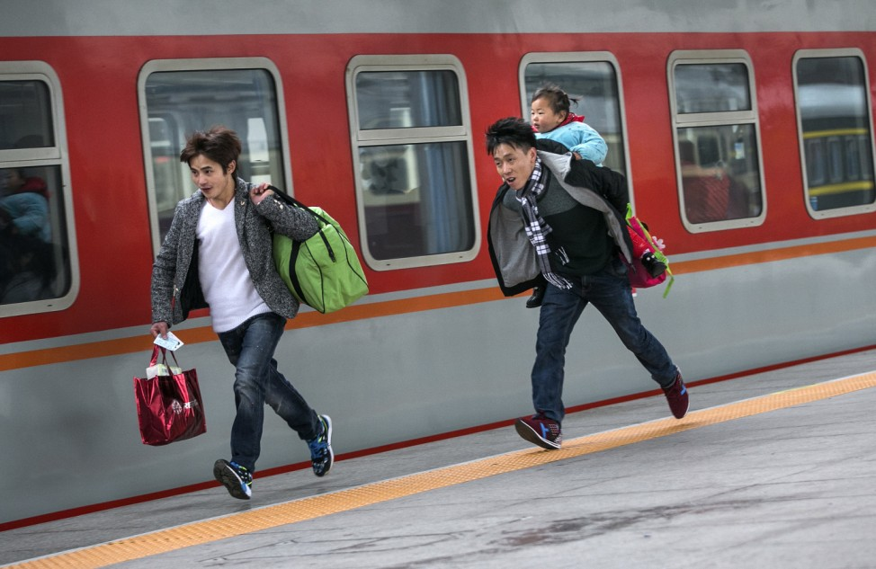 Passengers run to catch a train at a railway station in Hangzhou during the travel rush ahead of the upcoming Spring Festival