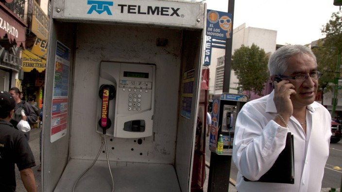 May 21 2012 Mexico City MEX A man uses his mobile phone next to a TELMEX public telephone in M