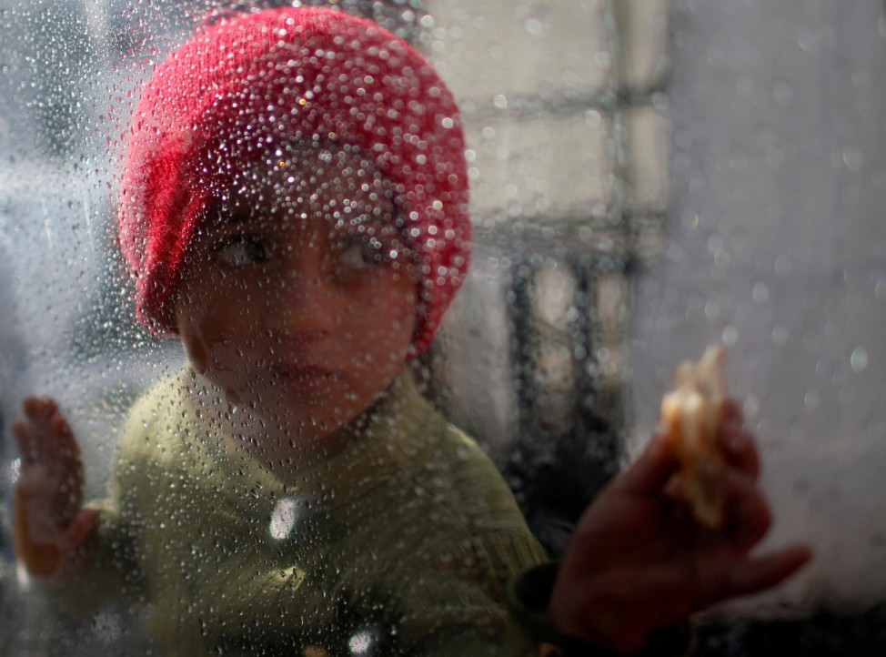 Palestinian girl looks through a plastic sheet as raindrops are seen, outside her family's house in Al-Shati refugee camp in Gaza City