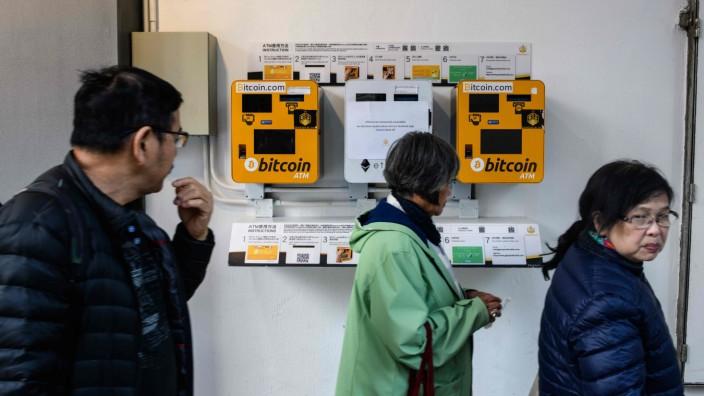 Kryptowährungen: Passanten betrachten zwei Bitcoin-Geldautomaten in Hong Kong. Wer ein derartiges Gerät in Deutschland sucht, wird wohl nicht mehr fündig. Die regulatorischen Hürden sind sehr hoch. In anderen europäischen Ländern wie Österreich oder Tschechien gibt es jedoch welche.
