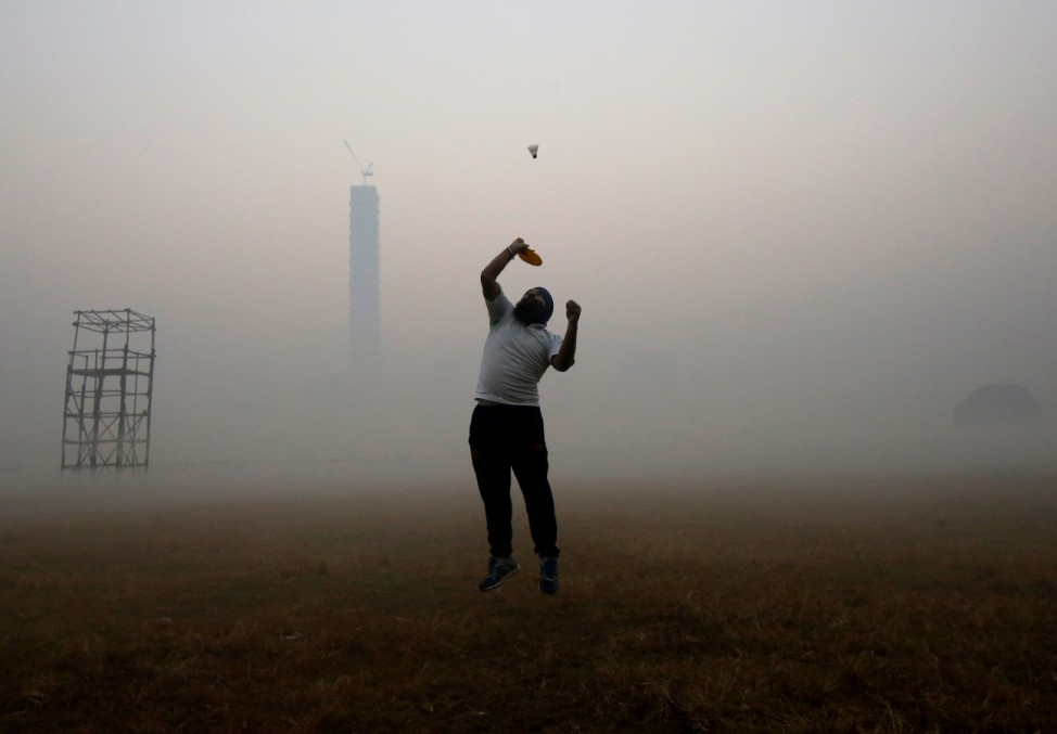 A man jumps to hit a shuttlecock inside a public park on a foggy winter morning in Kolkata