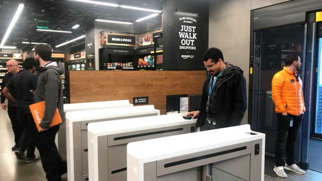 A shopper scans a smartphone app associated with his Amazon account and credit card information to enter the Amazon Go store in Seattle