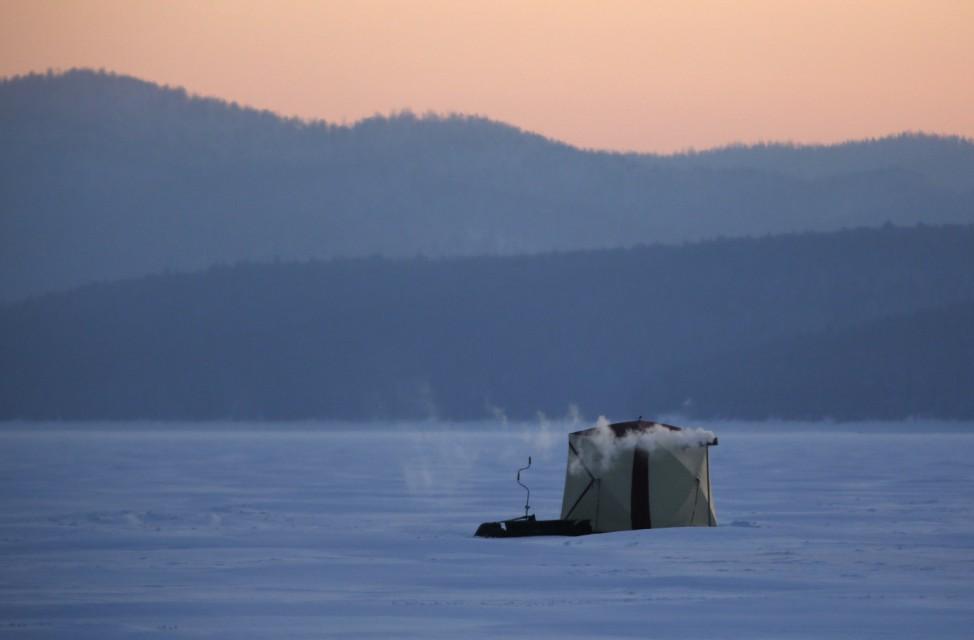 A tent of fishermen is seen on the ice-covered Yenisei River during sunset in the Siberian Taiga area outside Krasnoyarsk