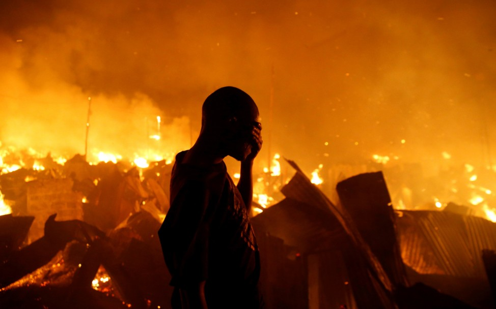 A resident reacts as he attempts to extinguish a fire that broke out at the Kijiji slums in the Southlands estate of Nairobi