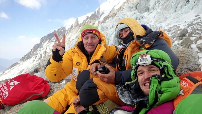 Denis Urubko, Elisabeth Revol, and Adam Bielecki pose for a picture at the base of the Diamir Face of Nanga Parbat