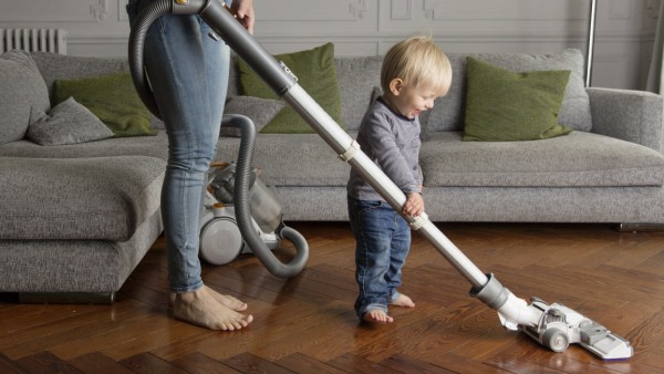 Laughing toddler helping his mother hoovering wooden floor model released Symbolfoto property releas
