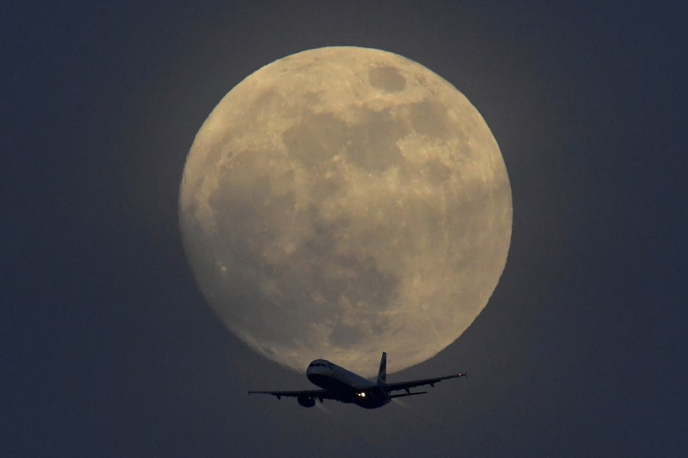 A British Airways aicraft flies infront of a full moon over London