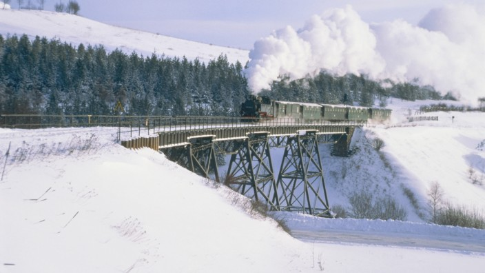 Train with steam locomotive driving through winter landscape in Erzgebirge mountains - Germany, m
