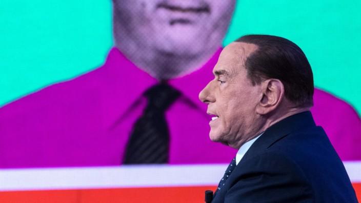 Italien: Berlusconi (hier bei einem Fernsehauftritt am Donnerstag in Rom) tritt wieder mal an. Skeptisch schaut der frühere Premierminister Matteo Renzi auf einem Bild im Hintergrund.