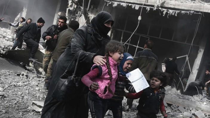 Naher Osten: Gewalt erzeugt Gegengewalt: Das Vorgehen der Regierung trifft vor allem die Zivilbevölkerung in den von Rebellen besetzten Gebieten. Im Bild: Eine Frau versucht sich samt Kindern in Sicherheit zu bringen. Die Bombardierung im Raum Hamouria forderte schon mehrere Dutzend Opfer.