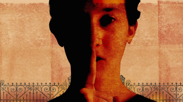 Ernste Frau mit Finger auf den Lippen in einem Zaun PUBLICATIONxINxGERxSUIxAUTxONLY RoyxScott 118003