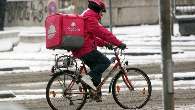Fahrradkurier vom Internet Portal Foodora liefert warme Speisen aus in der verschneiten Innenstadt F