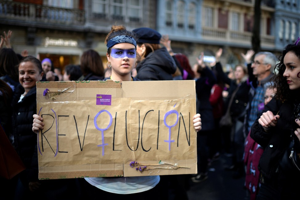 A protester holds a poster reading 'Revolution' during a demonstration for women's rights on International Women's Day, in Bilbao