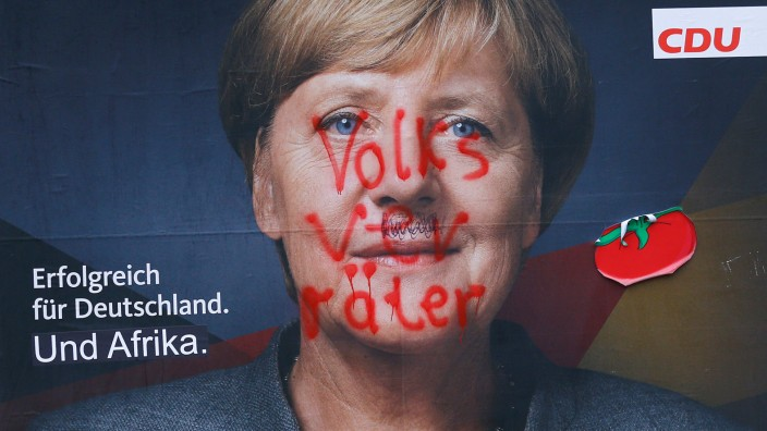 An election campaign poster of the Christian Democratic Union (CDU) party, with a headshot of German Chancellor Merkel, is painted with the word 'Volksverraeter' (People traitor) in Berlin
