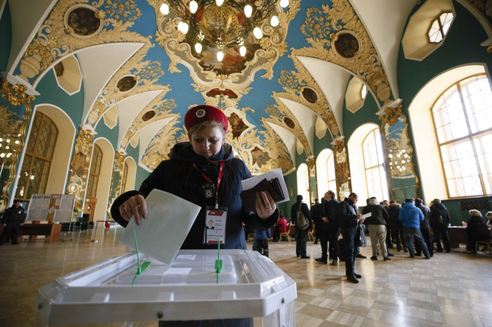 A voter casts her ballot inside a building of the Kazansky railway terminal during the presidential election in Moscow