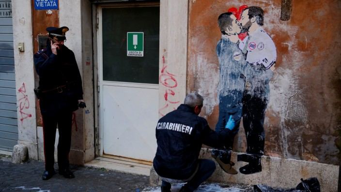 Italian Carabinieri work next to a mural depicting Northern League's leader Matteo Salvini and 5-Star Movement leader Luigi Di Maio kissing in Rome