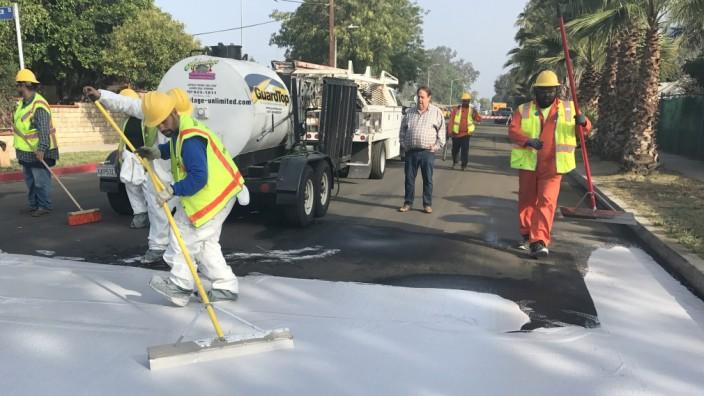 Umweltschutz: Bauarbeiter bringen reflektierenden Straßenbelag in Los Angeles auf.