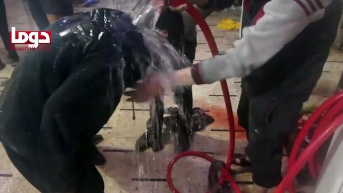 Syrienkrieg: Dieses Standbild aus einem Video zeigt nach Angaben des Douma City Coordination Committees, wie ein Opfer des mutmaßlichen Chemiewaffenangriffs mit Wasser behandelt wird.