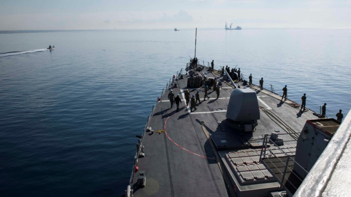 U.S. Navy sailors man the rails aboard the destroyer USS Donald Cook as the ship departs Larnaca