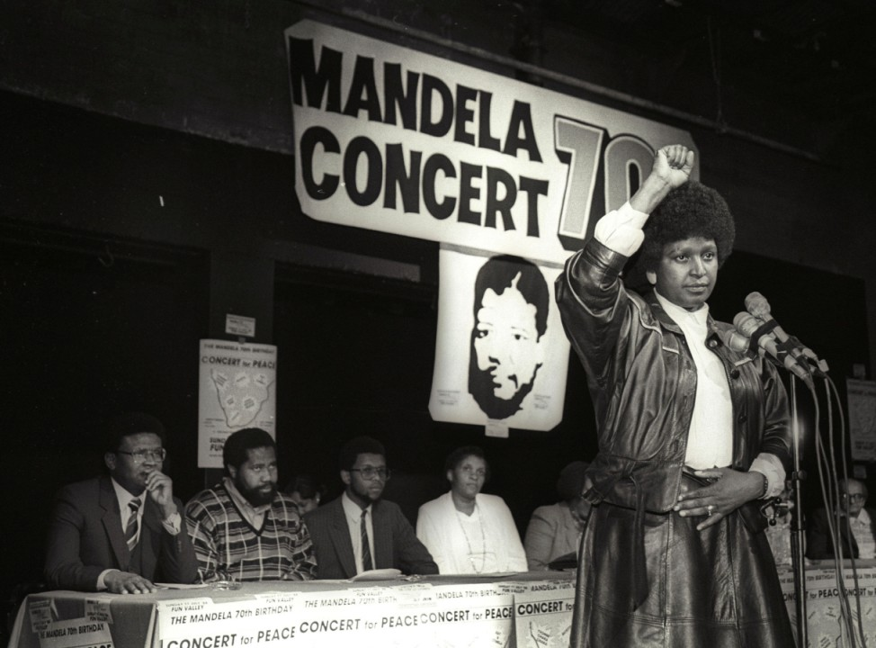 FILE PHOTO: Winnie Mandela raises her fist after announcing massive pop concert will be held to mark the 70th birthday of Nelson Mandela