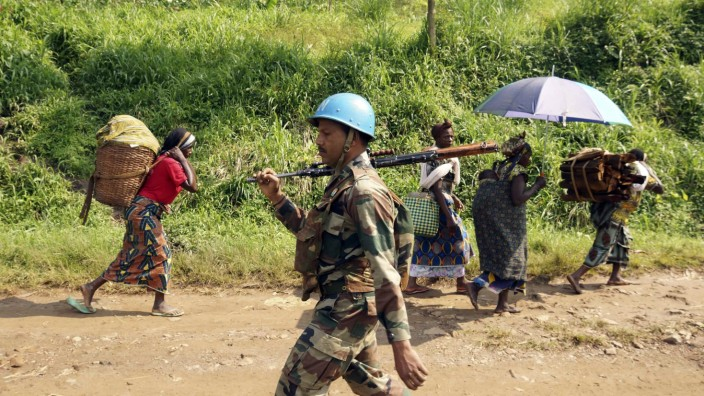 An Indian soldier, serving in MONUSCO, patrols past Congolese women walking to the market centre in Masisi