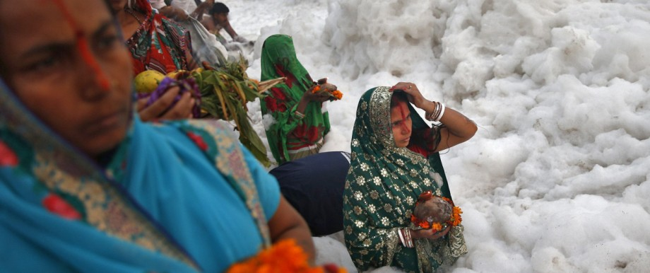 Hindu women worship the Sun god Surya in the polluted waters of the river Yamuna during the Hindu religious festival of Chatt Puja in New Delhi