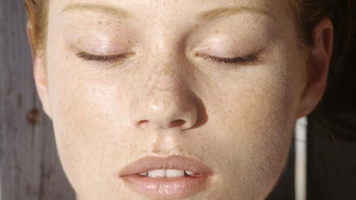 Young woman lying outdoors, sunbathing