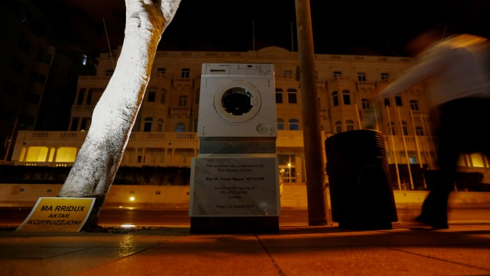 A washing machine and a mock plaque commemorating the opening of Pilatus Bank by Maltese PM Muscat in 2014, which was left outside Whitehall Mansions, which houses the Maltese-registered Pilatus Bank,  in Ta' Xbiex