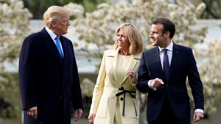 U.S. President Donald Trump speaks to French President Emmanuel Macron and Brigitte Macron on the South Lawn of the White House in Washington