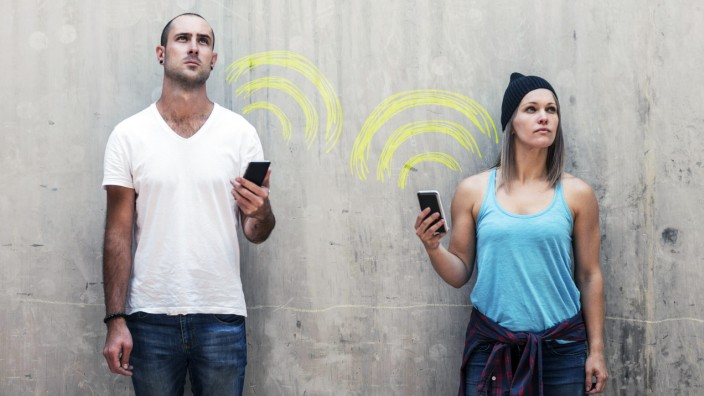 Man and woman holding their phones with wifi sign in chalk model released Symbolfoto property releas