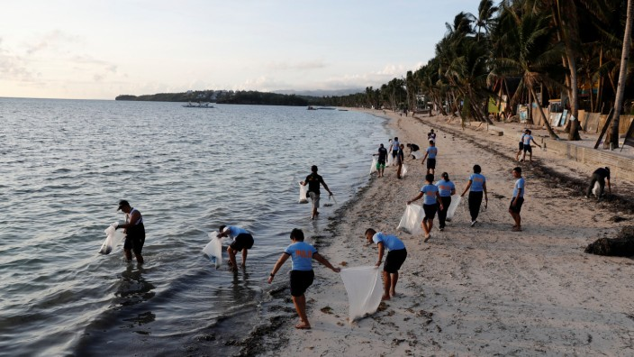 Policemen collect trash at Bulabog beach in the holiday island of Boracay during the first day of a temporary closure for tourists, in Philippines