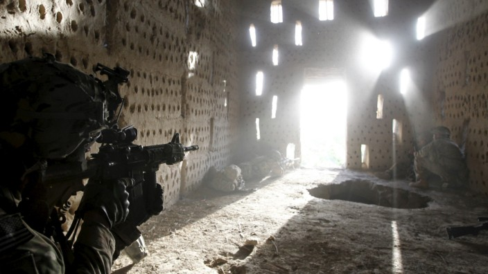 File photo of a U.S. soldier pointing his rifle after coming under fire in Zharay district in Kandahar province, southern Afghanistan